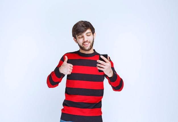 Человек в красной полосатой рубашке разговаривает по телефону и показывает палец вверх, слыша хорошие новости.
