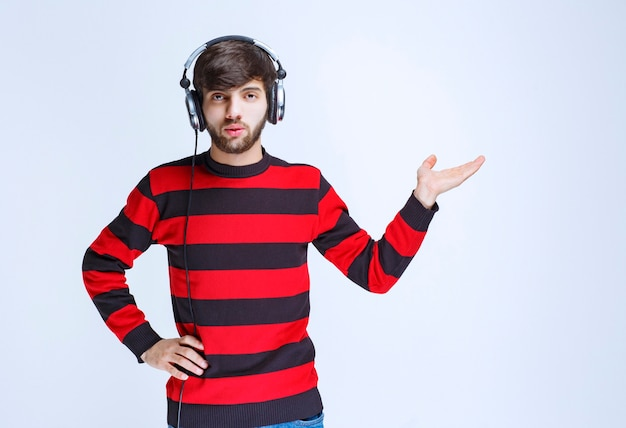 ヘッドフォンを着用し、右側を指している赤い縞模様のシャツの男。