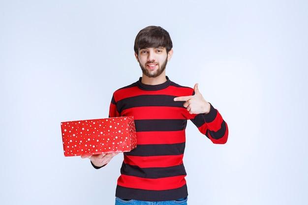 赤いギフトボックスと赤い縞模様のシャツを着て、誰かにそれを提示するように呼びかけている男。