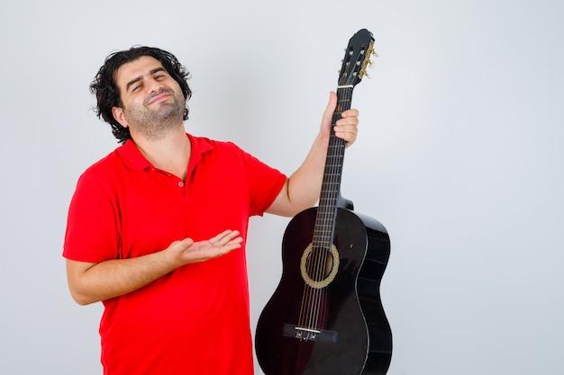 Человек в красной футболке показывает гитару и выглядит довольным