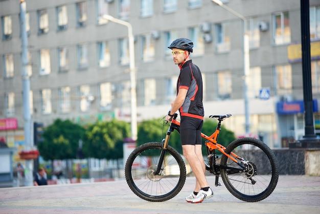 Человек в ослаблять после езды на велосипеде стоя близко велосипед перед зданием города. велосипедист смотрит далеко и позирует для спортивной одежды рекламной кампании.