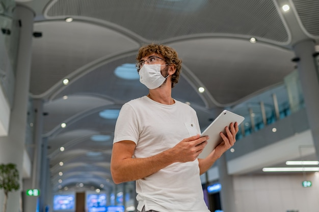 Человек в респираторной маске ждет следующего самолета в аэропорту и использует планшет.
