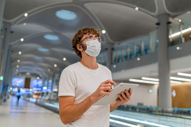 レスピレーターマスクの男が空港で次の飛行機を待っており、タブレットを使用しています。