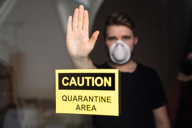 Человек в респираторной маске показывает стоп-жест