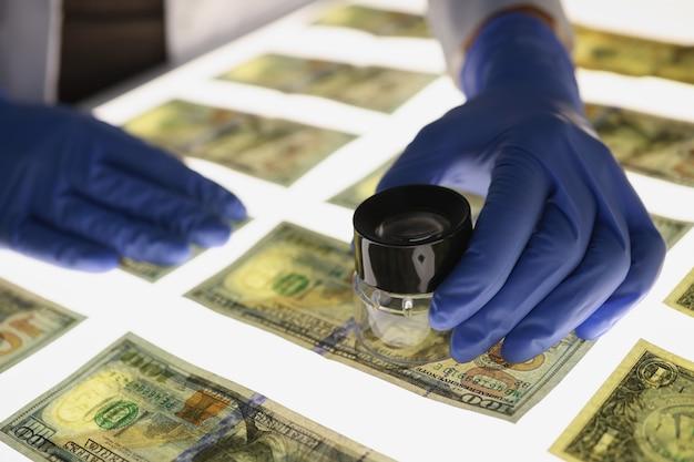 Человек в резиновых перчатках проверяет подлинность концепции фальшивых денег крупным планом американских долларовых купюр