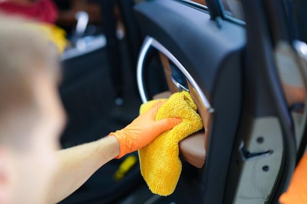 극세사 천으로 닫혀 있는 자동차 문에서 먼지를 닦는 고무 장갑을 낀 남자