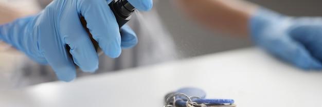 Человек в резиновых защитных перчатках надувает спрей с антисептиком на связке ключей крупным планом