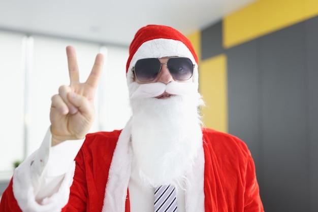 Мужчина в костюме санта-клауса с белой бородой и солнцезащитными очками держит пальцы в знак победы.