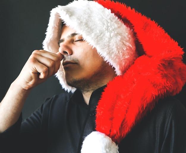 サンタクロースの帽子をかぶった男は、ヘロインを取っている彼の鼻を保持します。 2020年の新年。麻薬中毒者のディーラー。危険な習慣。不健康な生活の概念。
