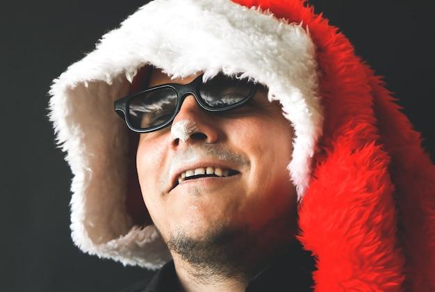 サンタクロースの男は麻薬を飲んでいます。ヘロインを取る男。 2020年の新年。危険な習慣。不健康な生活の概念。
