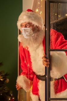 Человек в костюме санта-клауса с медицинской маской выходит через окно