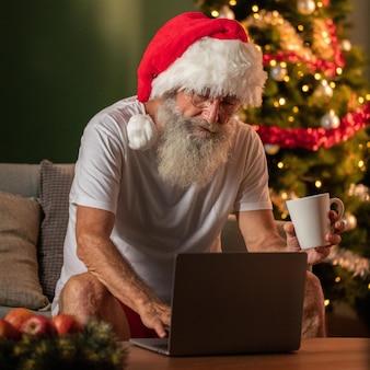 Человек в шляпе санта-клауса держит кружку и использует ноутбук дома