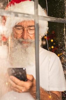 Человек в шляпе санта-клауса с помощью смартфона через окно