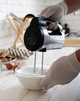 キッチンの電気ミキサーで卵白をホイップするサンタの帽子の男
