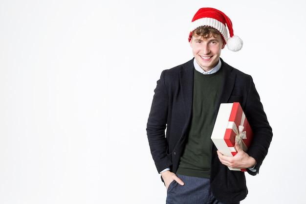 Человек в шляпе санта-клауса с красной подарочной коробкой