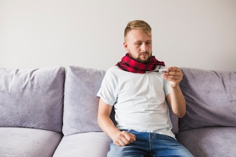 Man in scarf looking at thermometer