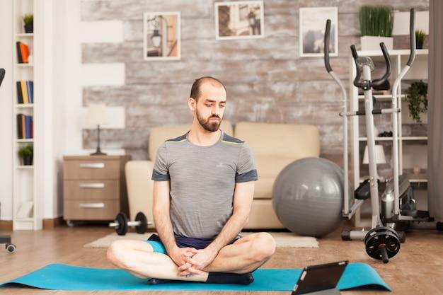 Мужчина в форме смотрит онлайн-урок йоги во время изоляции от коронавируса.