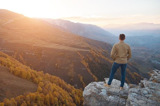 셔츠를 입은 남자는 가을 뒷면의 갈색 바위 언덕 꼭대기에 서 있는 색색의 숲과 들판이 있는 산 위로 일출을 감상합니다.