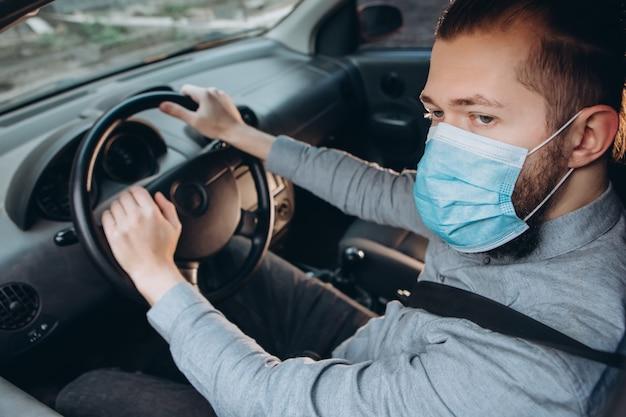 Человек в рубашке и медицинской маске сидит за рулем автомобиля.