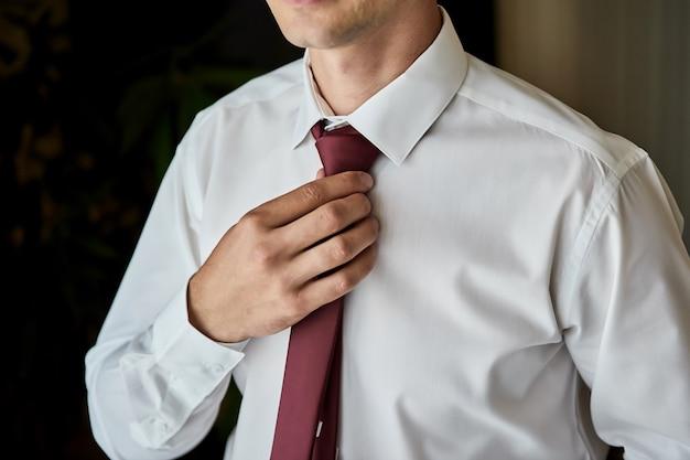 셔츠를 차려 입고 집에서 목에 넥타이를 조정하는 남자. 남성 패션