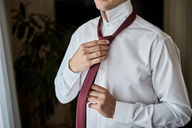 셔츠 차려 입고 집에서 목에 넥타이를 조정하는 남자