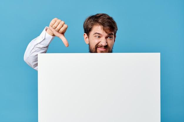 青い背景にプロモーション看板を保持しているシャツの男。