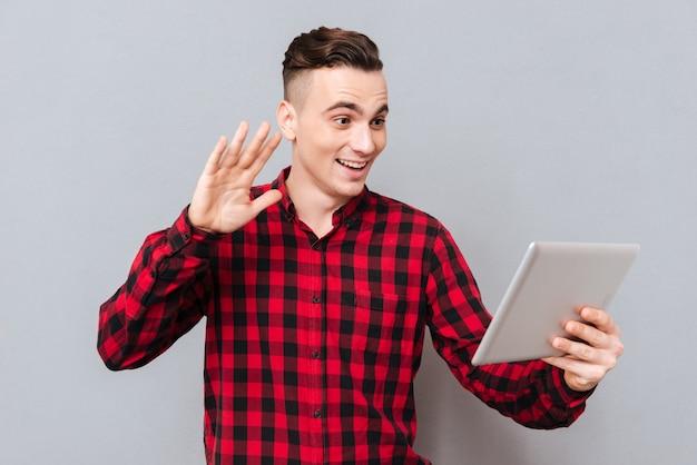 한 손에 태블릿 컴퓨터를 들고 셔츠를 입은 남자가 태블릿에서 두 번째 손을 흔들고 있습니다. 격리 된 회색 배경