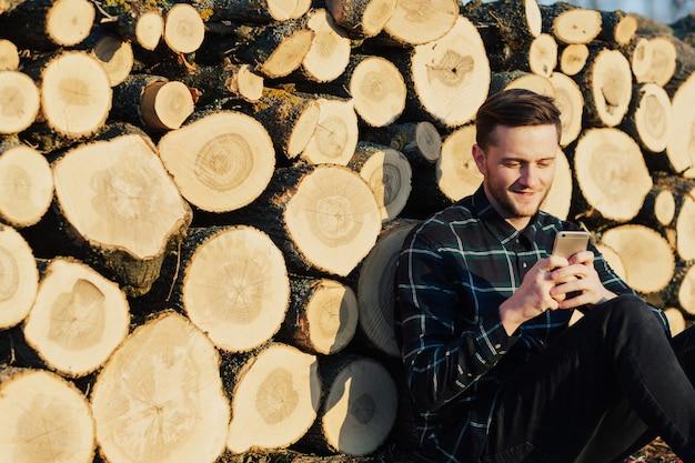 シャツを着た男は木の丸太の背景にスマートフォンを使用しています