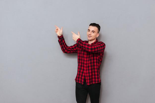 Человек в рубашке указывая пальцами прочь. изолированный серый фон