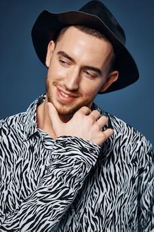 Мужчина в рубашке в черной шляпе позирует в элегантном стиле моды