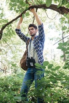 Человек в рубашке с биноклем и рюкзаком
