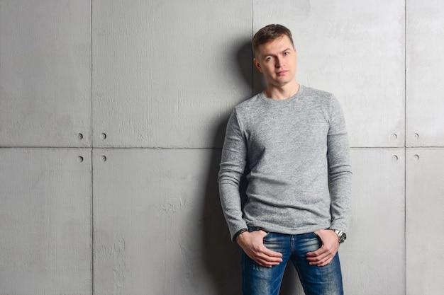 シンプルなカジュアルな服装の男性、セーターとジーンズは、灰色のコンクリートの壁にもたれかかっています