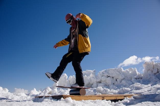 Человек в лыжном снаряжении и защитных очках балансирует на сноуборде