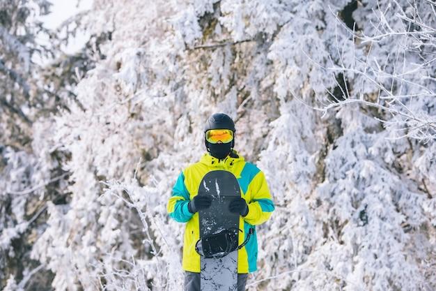 프레임 중앙에 스노우보드 겨울 여가 활동이 있는 스키 장비를 입은 남자