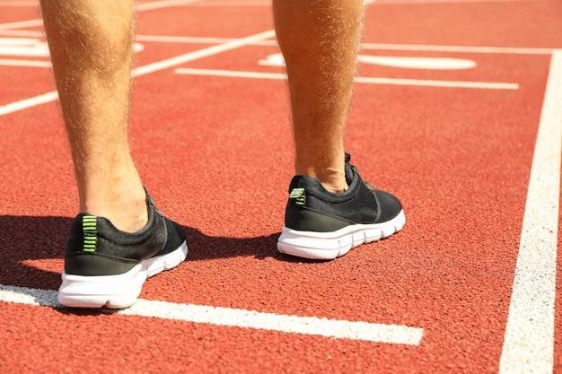 Человек в кроссовках на красной спортивной беговой дорожке, крупный план