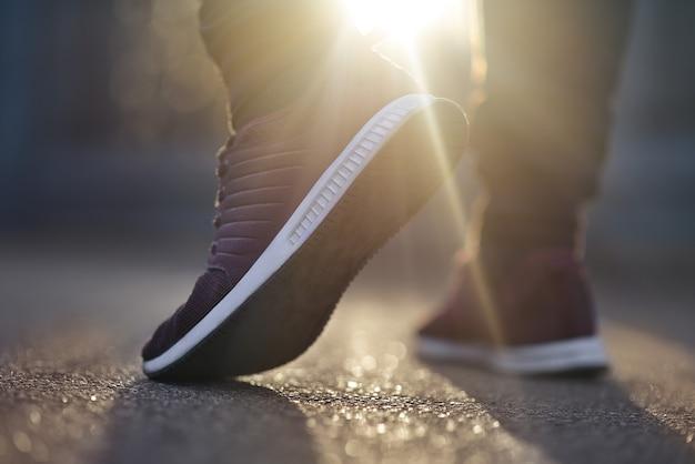 운동화를 입은 남자가 화창한 날에 길을 걷고 있습니다.