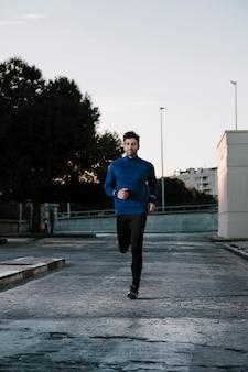 通りにジョギングするスポーツウェアの男性
