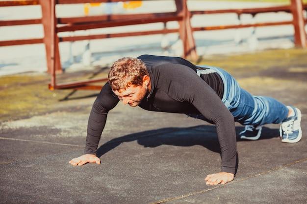 운동복을 입은 남자가 야외에서 푸시업을 수행합니다. 건강하고 스포츠 라이프 스타일