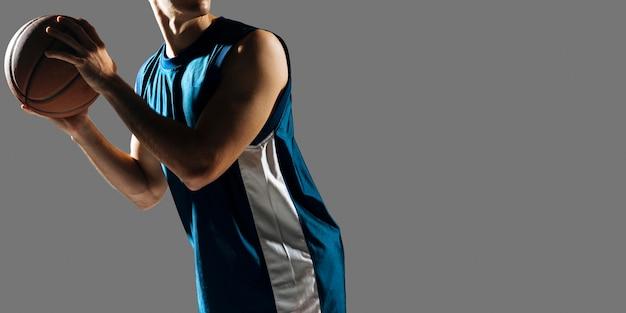 Человек в спортивной одежде играет в баскетбол с копией пространства