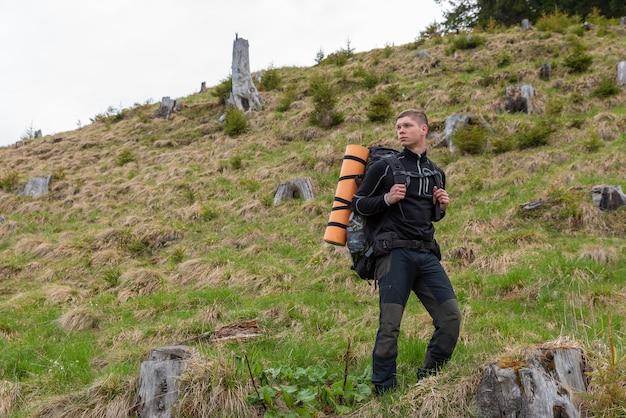 自然の中で彼の肩にバックパックでポーズスポーツウェアの男