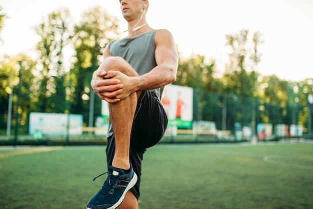 스포츠웨어에 남자는 야외 피트니스 운동을 준비합니다. 공원에서 훈련에 강한 스포츠맨