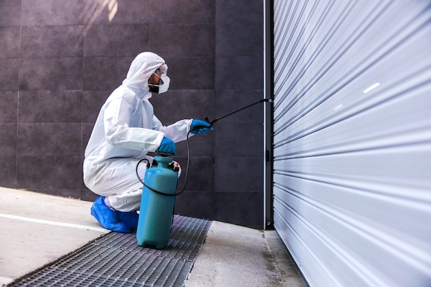 コロナウイルスの拡散を防ぐためにゴム手袋をかがめて消毒用ガレージのドアを使ってスプレーする滅菌手袋の男性。