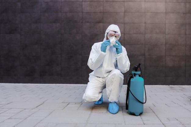 Мужчина в стерильной защитной форме с резиновыми перчатками приседает на открытом воздухе и надевает защитную маску на лицо. рядом с ним распылитель с дезинфицирующим средством. профилактика распространения концепции вируса короны.