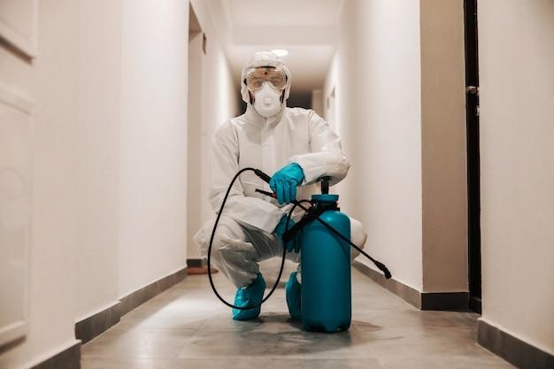 建物のホールでしゃがみ、消毒剤で噴霧器を保持している滅菌スーツの男