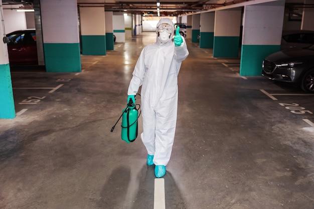 建物のホールを消毒する滅菌スーツを着た男。コロナの概念からの保護。