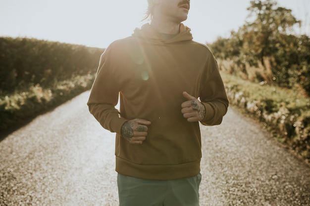 日没時に田舎でジョギングする伸縮性のあるパーカーの男