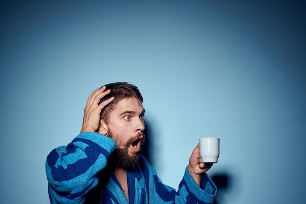 Мужчина в полосатом синем халате с белой чашкой в руке удивился
