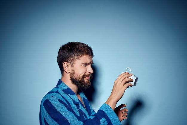 Человек в полосатом синем халате, держа в руке белую чашку