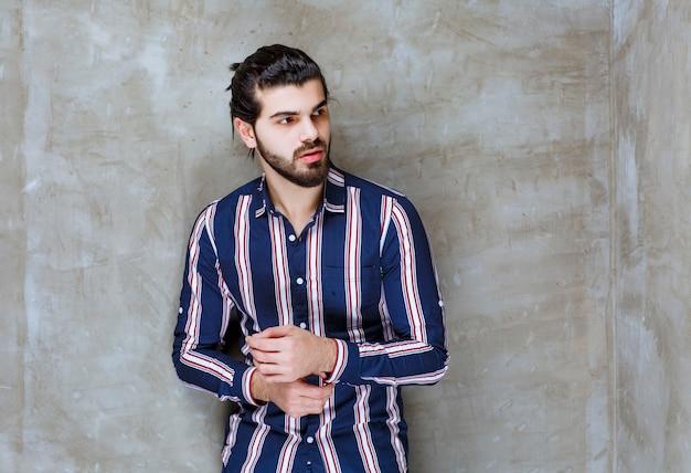 彼のボタンを閉じる縞模様のシャツの男。