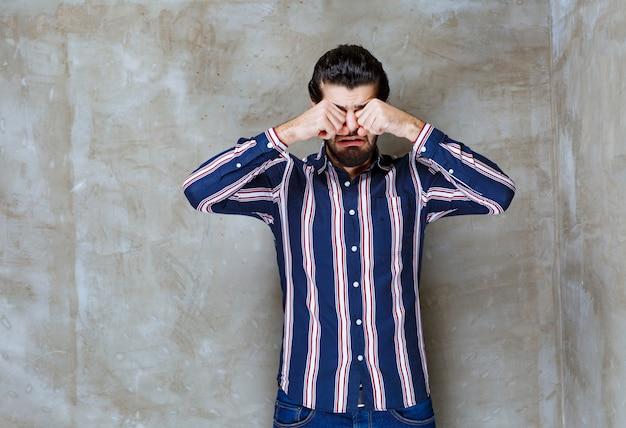 縞模様のシャツを着た男が泣いて悲しんでいます。